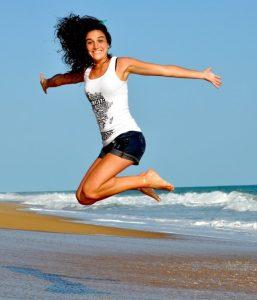 Frau am Strand springt